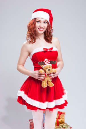 Positive Caucasian Santa Helper With Christmas Gift in Hands