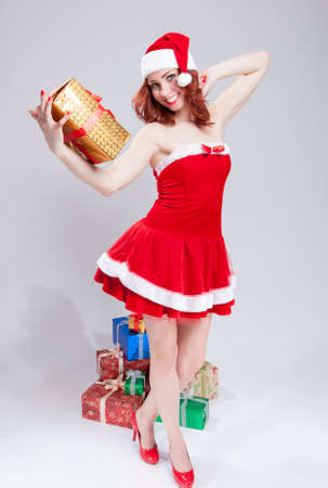 Holidays Concept and Ideas. Happy Smiling Caucasian Red Haired Santa Helper Holding Golden Gift in Hand.Penty of Gifts Behind.Vertical Image