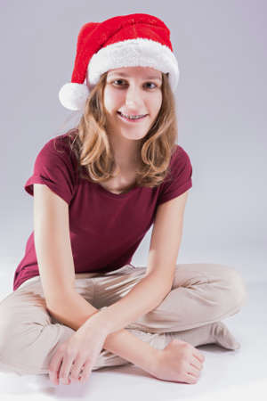 Smiling Teenage Girl in Santa Hat Wearing Dental Teeth Brackets. Sitting Against White Background. Vertical Image photo