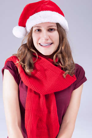 Dental Treatment Concepts and Ideas. Caucasian  Teenager in Santa Hat With Teeth Brackets Against White. Vertical Image Composition photo