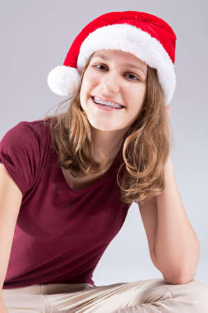 Dental Concepts and Ideas. CHappy Caucasian  Teenager in Santa Hat With Teeth Brackets. Sitting. Vertical Image Composition photo