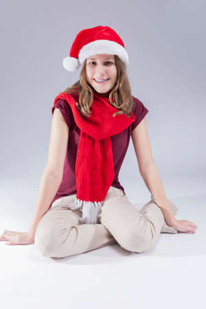 Dental Concepts and Ideas. CHappy Caucasian  Teenager in Santa Hat With Teeth Brackets. Sitting on Floor Against White. Vertical Image Composition photo