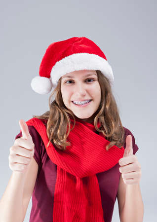 Dental Treatment Concepts. Happy  Smiling Caucasian  Teenager in Santa Hat With Teeth Brackets Posing Against White Background. Vertical Image photo