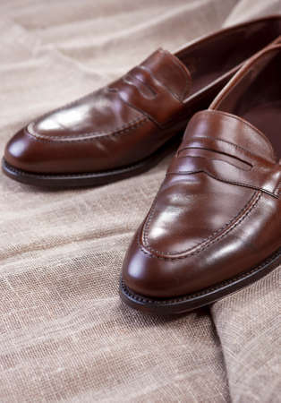 loafer: Shoes Concepts and Ideas. Closeup of Stylish Modern Brown Leather Penny Loafer Shoes On Mesh Surface.Vertical Image Orientation Stock Photo