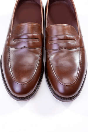 loafer: Footwear Concepts. Pair of Stylish Brown Penny Loafer Shoes Against White Background. Placed Together Closely. Vertical Image Composition