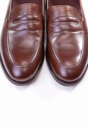 loafer: Footwear Concepts. Pair of Stylish Brown Penny Loafer Shoes Against White Background. Placed Together Closely. Vertical Image Orientation Stock Photo