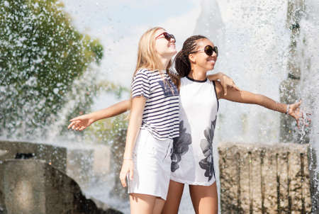 Teenagers Concepts. Two Teenage Girfriends Embracing Together. Posing Against Fountain in Park Outdoors. African American Model and Caucasian Blond Model.Horizontal Image Composition photo