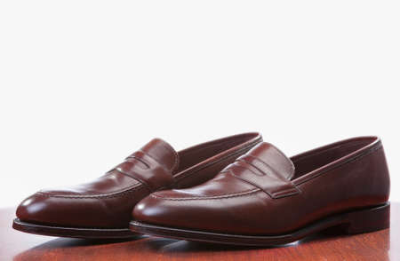 loafer: Footwear Concepts. Closeup of Pair of Stylish Brown Penny Loafer Shoes Against White. Placed on Wooden Reflecting Surface. Horizontal Image Stock Photo