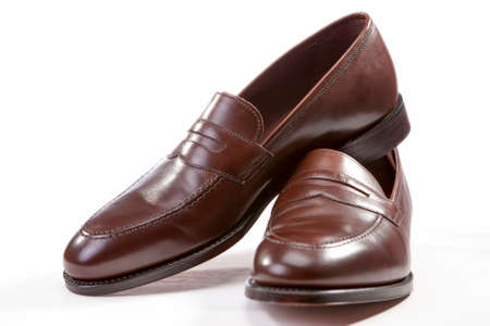 loafer: Footwear Concepts. Leather Stylish Brown Penny Loafer Shoes Together Against White Background. Horizontal Image