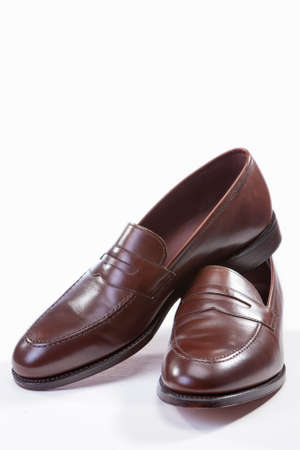 loafer: Footwear Concepts. Leather Stylish Brown Penny Loafer Shoes Together Against White Background. Vertical Image Orientation