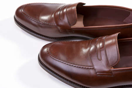 loafer: Footwear Concepts. Closeup of Pair of Stylish Brown Penny Loafer Shoes Against White Background. Above View. Horizontal Image