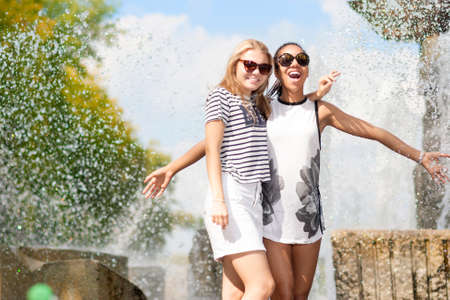 Teenagers Concepts. Two Funny and Laughing Teenage Girfriends Embracing Together. Posing Against Fountain in Park Outdoors. African American Model and Caucasian Blond Model.Horizontal Image Composition photo