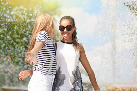 Teenagers Concepts and Ideas. Two Teenage Girfriends Embracing Together. Posing Against Fountain in Park Outdoors. African American Model and Caucasian Blond Model.Horizontal Shot photo
