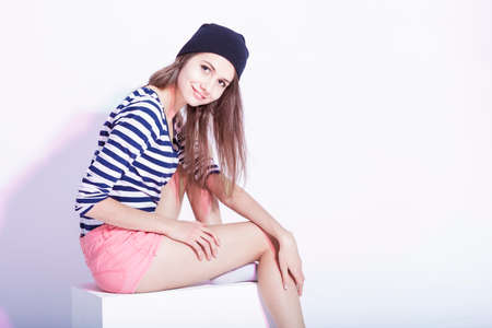 Youth Lifestyle Concepts. Portrait of Happy Caucasian Fashionable Brunette in Hat and Striped Shirt Posing in Studio Against White. Horizontal Image Orientation
