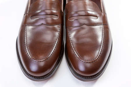 loafer: Footwear Concepts. Pair of Stylish Brown Penny Loafer Shoes Against White Background. Placed Together Closely. Horizontal Image Composition