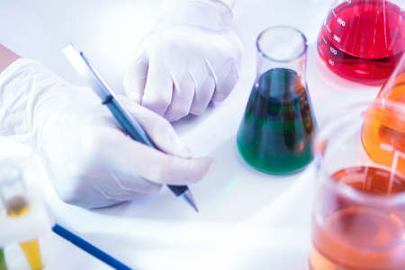 Closeup of hands of Female Laboratory Worker Dealing With Flasks Containing Liquid Chemicals. Horizontal Image Composition Stock Photo
