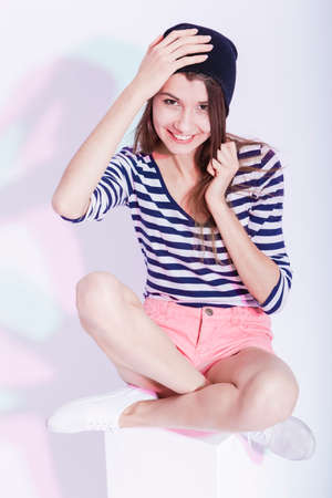 smiing: Youth Lifestyle Concepts and Ideas. Portrait of  Happy Smiing Caucasian Brunette in Hat and Striped Shirt Posing in Studio Against White. Vertical Image Composition