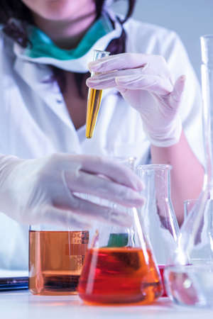 Closeup of hands of Female Laboratory Worker Dealing With Flasks Containing Liquid Chemicals.Vertical Image Composition