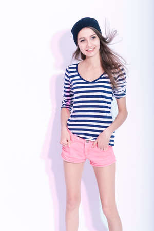 Fashion Lifestyle Concepts and Ideas. Portrait of Smiling Happy Slim Brunette Girl Wearing Hat and Striped Shirt. Posing in Studio Against White. Vertical Composition