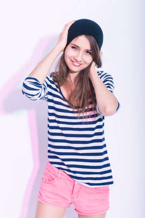Youth LIfestyle Concepts and Ideas. Natural Portrait of Cute and Smiling Slim Caucasian Brunette Girl in Hat and Striped Shirt. Posing Against White Background. Hands Lifted Near Head. Vertical Image