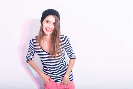 Natural Portrait of Happy Laughing Caucasian Brunette Girl in Hat and Striped Shirt. Posing Against White Background.Horizontal Image Imagens