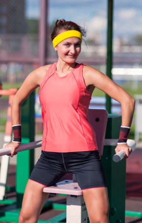 Portrait ot Caucasian Brunette Female Athlete in   Professional Outfit Having Work Out Exercise Outdoor.Vertical Image Composition