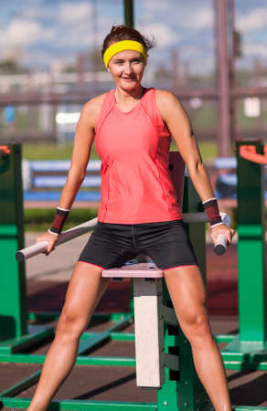 Sport Ideas. Portrait ot Caucasian Brunette Female Athlete in   Professional Outfit Having Work Out Exercise Outdoor.Vertical Image Composition