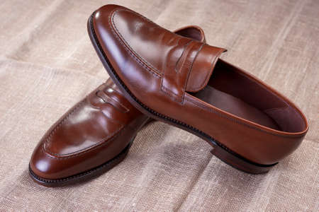 loafer: Footwear Concepts and Ideas. Pair of Brown Stylish Leather Penny Loafer Shoes Placed On Mesh Surface. Horizontal Image Composition Stock Photo