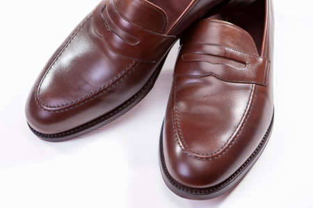 loafer: Footwear Concepts. Closeup of Pair of Stylish Brown Penny Loafer Shoes Against White Background. Horizontal Image Orientation Stock Photo