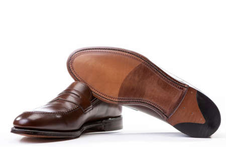 loafer: Footwear Concepts. Pair of Stylish Brown Penny Loafer Shoes Against White Background with One Item Reversed. Horizontal Image Composition Stock Photo