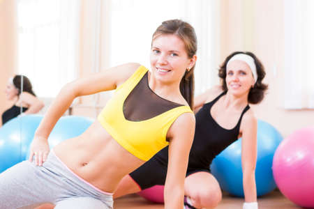 bodycare: Sport, Fitness, Healthy Lifestyle Concepts.Two Female Caucasian Athletes in Good Fit Posing With Fitballs in Sport Gym.Horizontal Image Composition