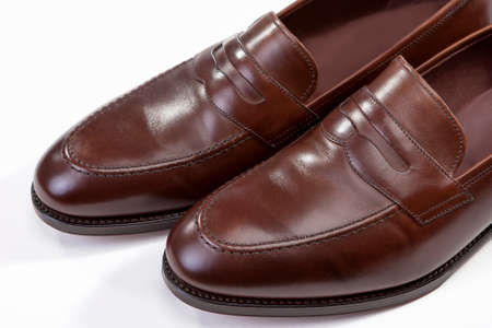 loafer: Footwear Concepts. Extreme Closeup of Leather Stylish Brown Penny Loafer Shoes Tips Against White Background. Horizontal Image Orientation Stock Photo