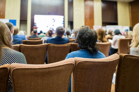 Group of Professionals Attending Business Conference. Sitting in Front of The Big Screen on Stage. Horizontal Image Stock Photo
