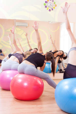 bodycare: Sport, Fitness, Helathy Lifestyle Concepts. Group of Five Caucasian Female Athletes Having Stretching Exercises with Fitballs Indoors. Vertical Image Composition Stock Photo