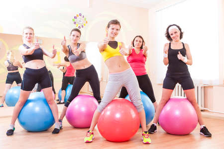 bodycare: Sport and Fitness Concepts. Group of Five Caucasian Female Athletes Having Exercises With Fitballs in Gym and Showing Thumbs Up Sign. Horizontal Image Orientation
