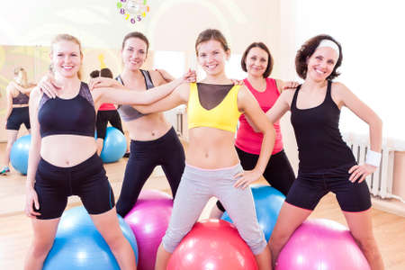 bodycare: Sport and Healthy Lifestyle Concepts. Group of Five Happy Caucasian Female Athletes Posing Together Embraced Against Fitballs in Gym.Horizontal Image Composition