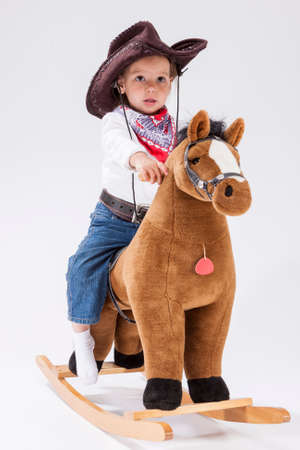 Children Consepts. Little Caucasian Girl Posing in Cowgirl Clothing with Toy Horse Against White Background.Vertical Image
