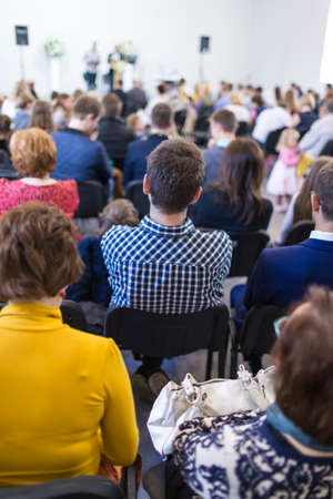 Groep mensen zitten in de hal tijdens een conferentie. Twee mannelijke gastheren spreken op het podium voor het publiek. Verticale opname Stockfoto