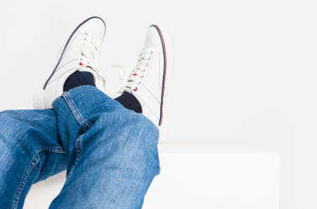 Closeup Shot of Mens Legs on White Fashion Sneakers and Jeans Laid on High Support.Horizontal Image Фото со стока