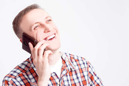 street shot: Youth Lifestyle Concepts and Ideas.Closeup  Portrait of Smiling Happy Caucasian Man Speaking on Cellphone. Posing Against White Background. Horizontal Image