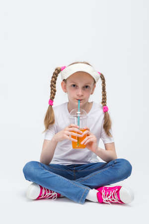 Kid Ideas and Concepts. Portrait of Pretty Caucasian Blond Girl wearing Visor Sitting on Floor with Cup of Juice and Drinking Through Straw. Vertical Image Stock Photo