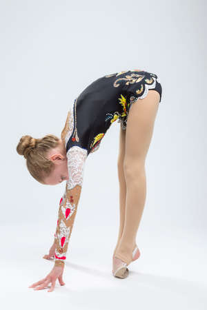 Sport Ideas. Young Caucasian Female Rhythmic Gymnast Athlete In Professional Competitive Suit Doing Backbend Stretching Exercise While Posing in Studio Against White. Vertical Image Фото со стока - 81855186