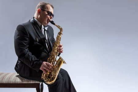Music Concepts. Portrait of Mature Relaxed and Thoughful Caucasian Saxophone Player in Sunglasses Playing the Saxophone While Sitting on Chair in Studio Environment. Horizontal Image Stock Photo