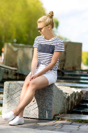 Teenager Concepts. Portrait of Shy and Sensual Caucasian Teenage Girl Posing in  Green Summer Park and Wearing  Sunglasses. Sitting on Long Stone. Vertical Image Composition photo