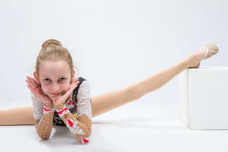 Sportkonzepte und Ideen. Junger kaukasischer weiblicher rhythmischer Gymnast-Athlet in der professionellen wettbewerbsfähigen Klage, die aufgespaltete Übung bei der Aufstellung im Studio gegen Weiß tut. Horizontale Bildausrichtung Standard-Bild - 82444316