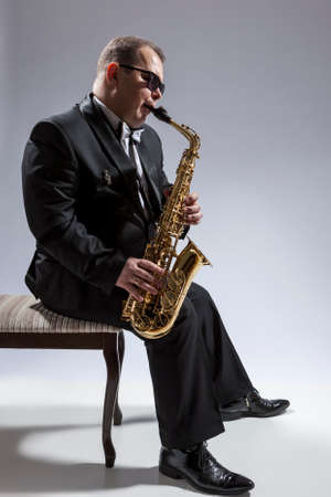 Music Concepts. Portrait of Mature Relaxed and Thoughful Caucasian Saxophone Player in Sunglasses Playing the Saxophone While Sitting on Chair in Studio Environment. Vertical Image Composition