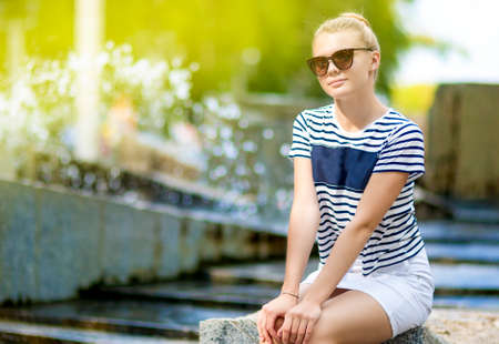 Teenager Concepts. Portrait of Shy and Sensual Caucasian Teenage Girl Posing in  Green Summer Park and Wearing  Sunglasses. Sitting on Long Stone. Horizontal Image Composition photo