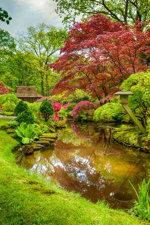 the hague: Picturesque Scenery of Japanese Garden with Asian Zen Sculptures  on Background in the Hague (Den Haag) in the Netherlands Straight After the Rain. Vertical Image Stock Photo