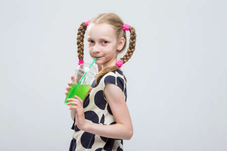greeen: Cute And smiling Caucasian LIttle Girl With Pigtails Posing in Polka Dot Dress with Cup of Greeen Juice. Drinking Through Straw. Horizontal Image Orientation