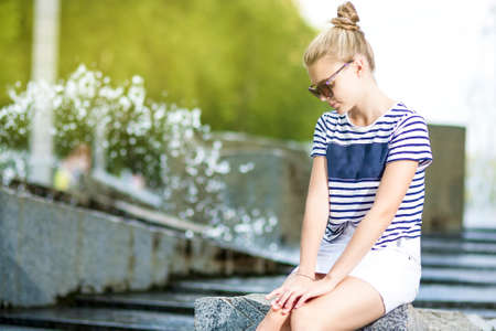 Portrait of Shy and Sensual Caucasian Teenage Girl Posing in  Green Summer Park and Wearing  Sunglasses. Sitting on Long Stone. Horizontal Image Orientation photo
